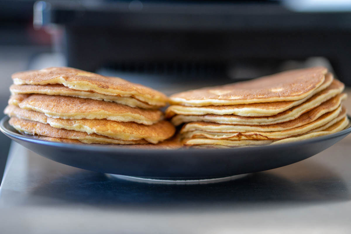 Two stacks of almond flour pancakes, the one on the left with beaten egg whites, the one on the right-hand side without.