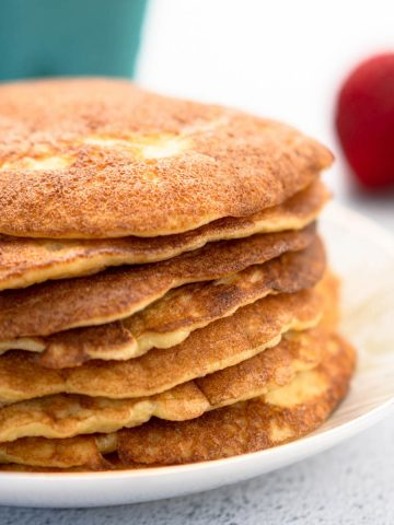 Stack of almond flour pancakes on plate with strawberry in background.