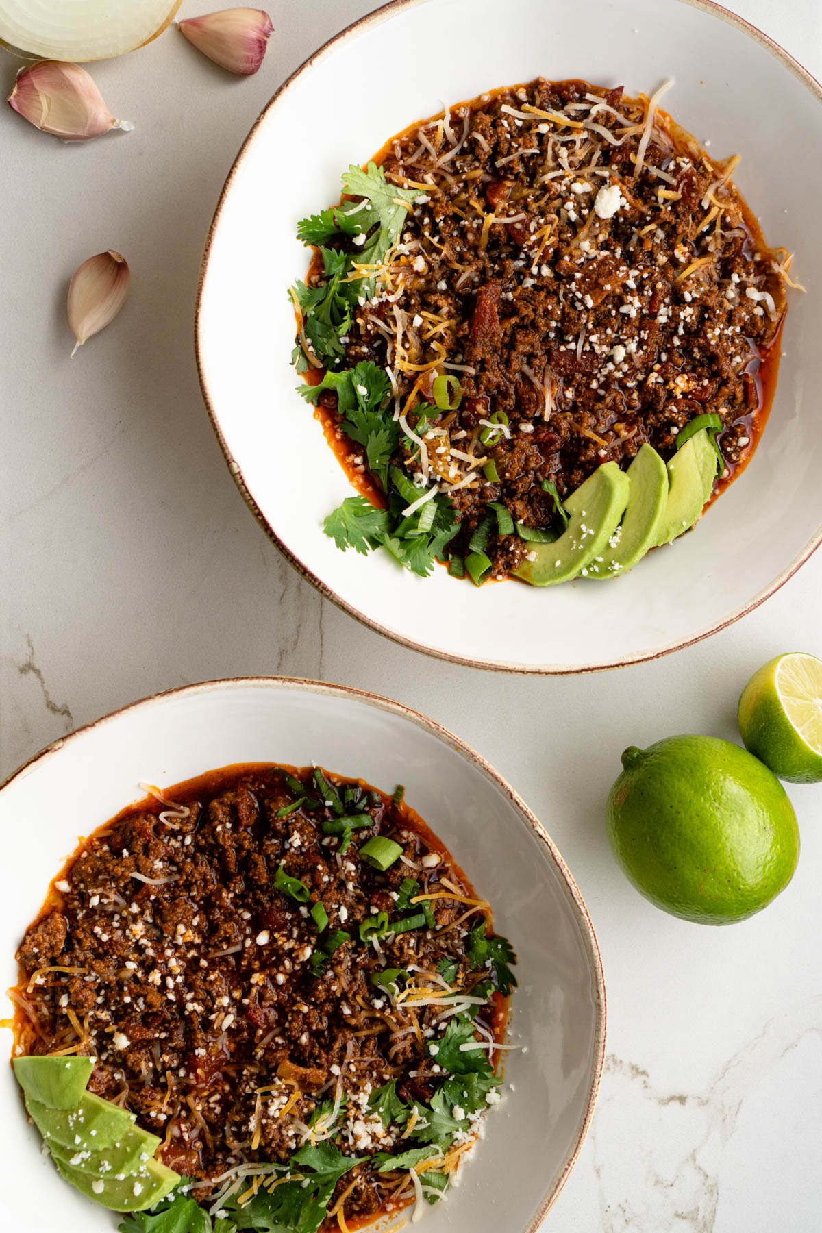 Two bowls of chili near garlic cloves and lime