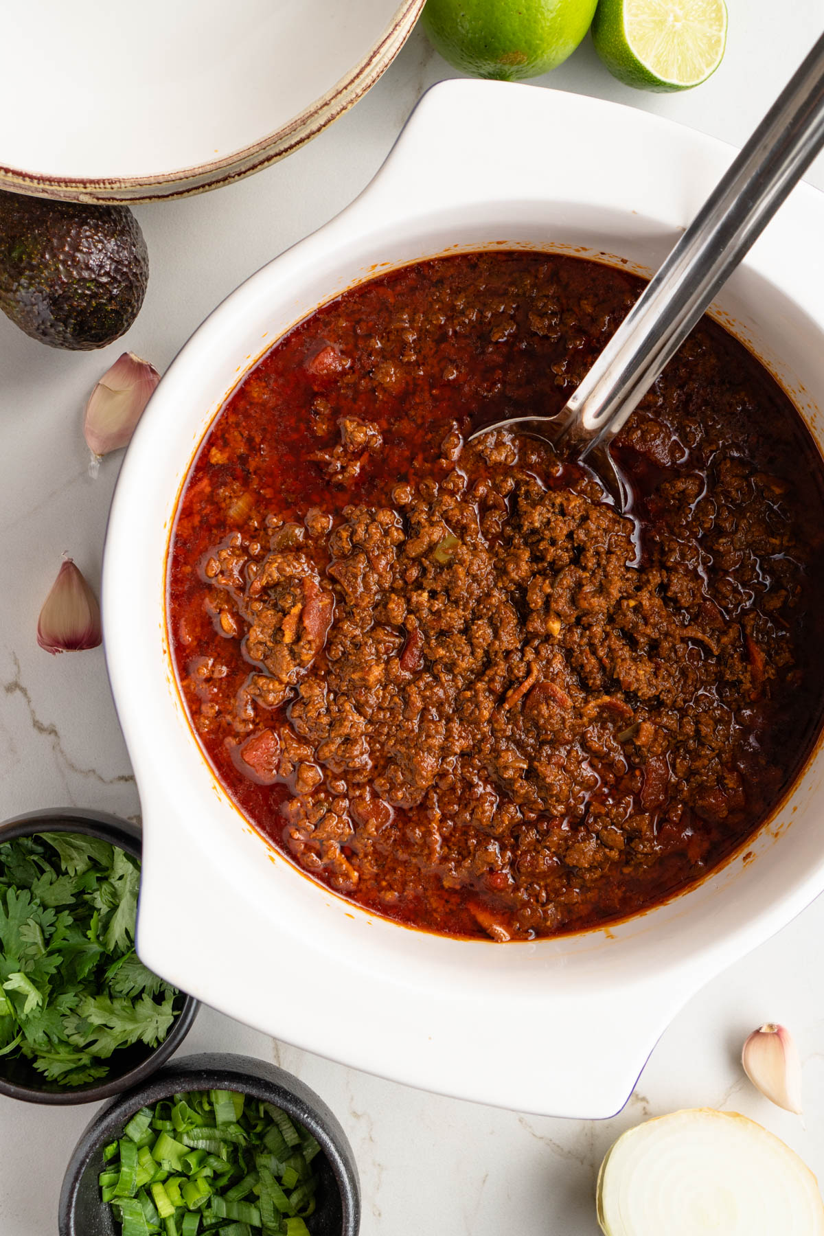 Full pot of chili with serving spoon.