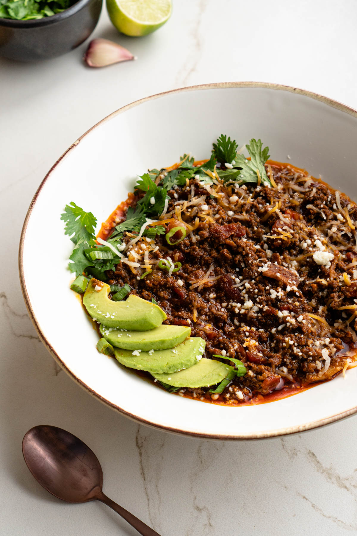 Keto chili con carne with avocado slices, cilantro, green onion, and cheese toppings.