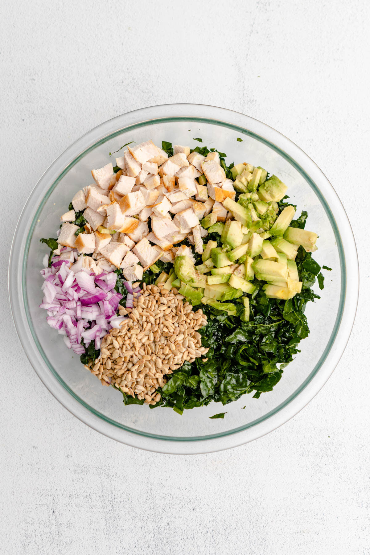 Chopped ingredients on top of massaged kale leaves before tossing salad together.