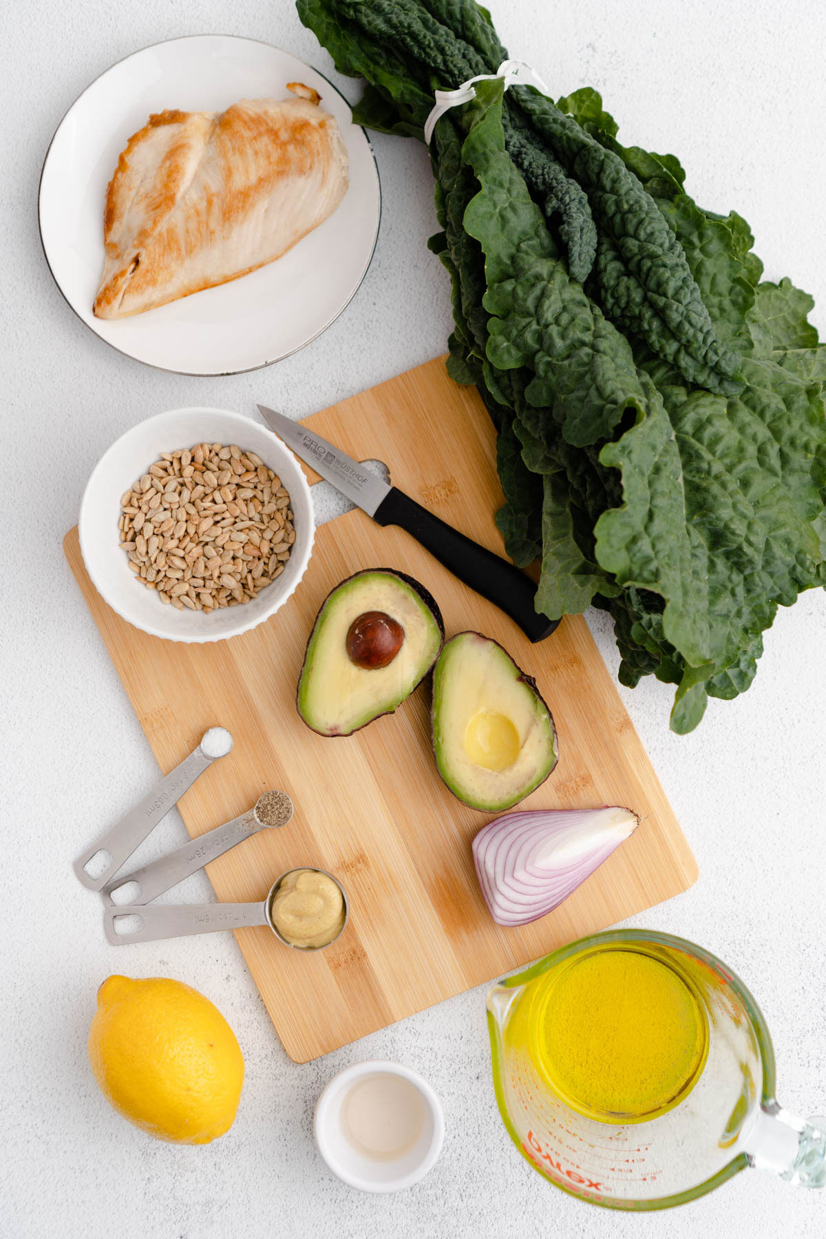 Overhead shot of ingredients used to prepare recipe: kale bunch, chicken breast on plate, olive oil in cup, lemon, cut avocado and red onion.