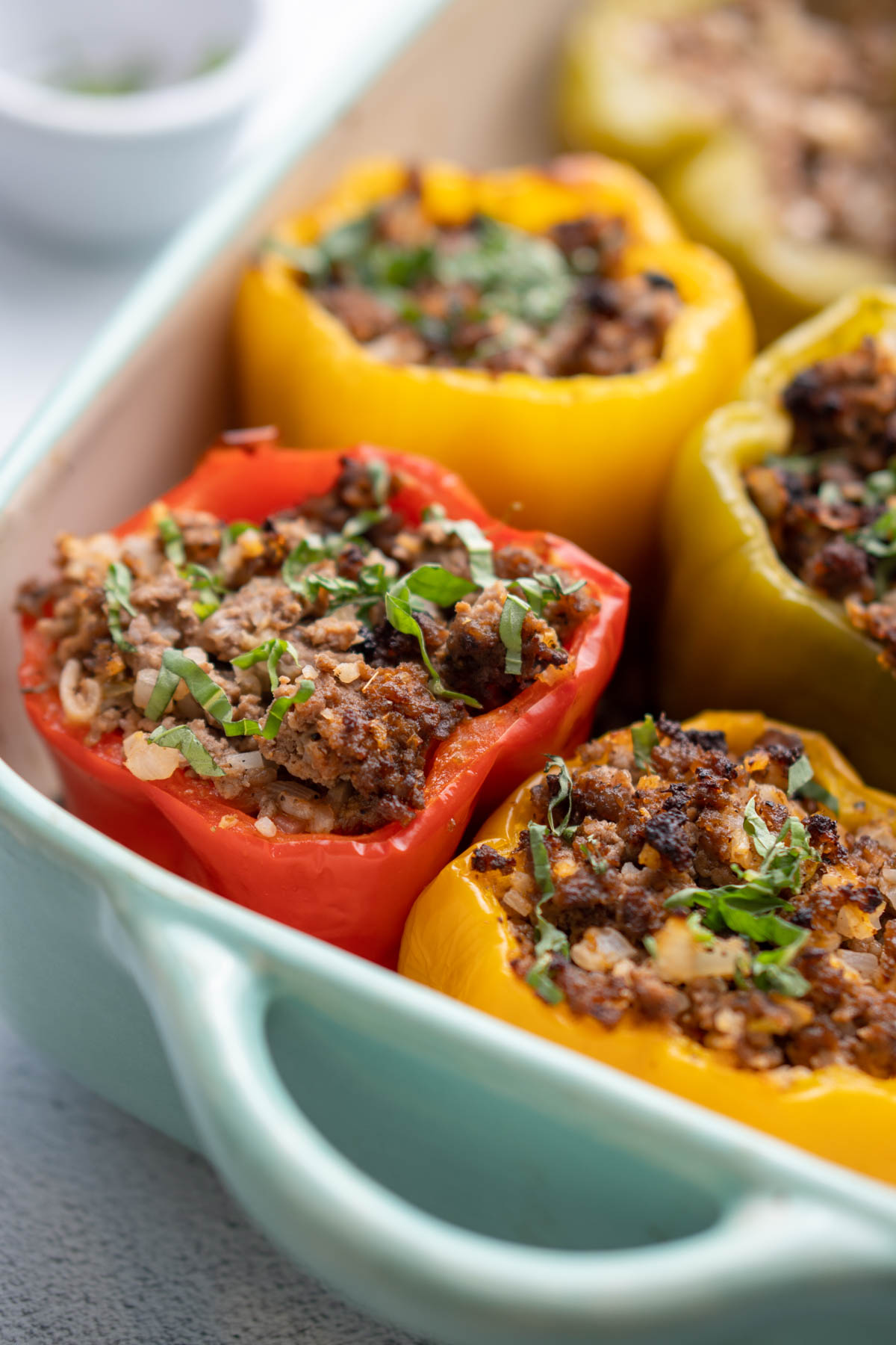 Bell peppers stuffed with ground beef mixture in casserole dish garnished with fresh basil.