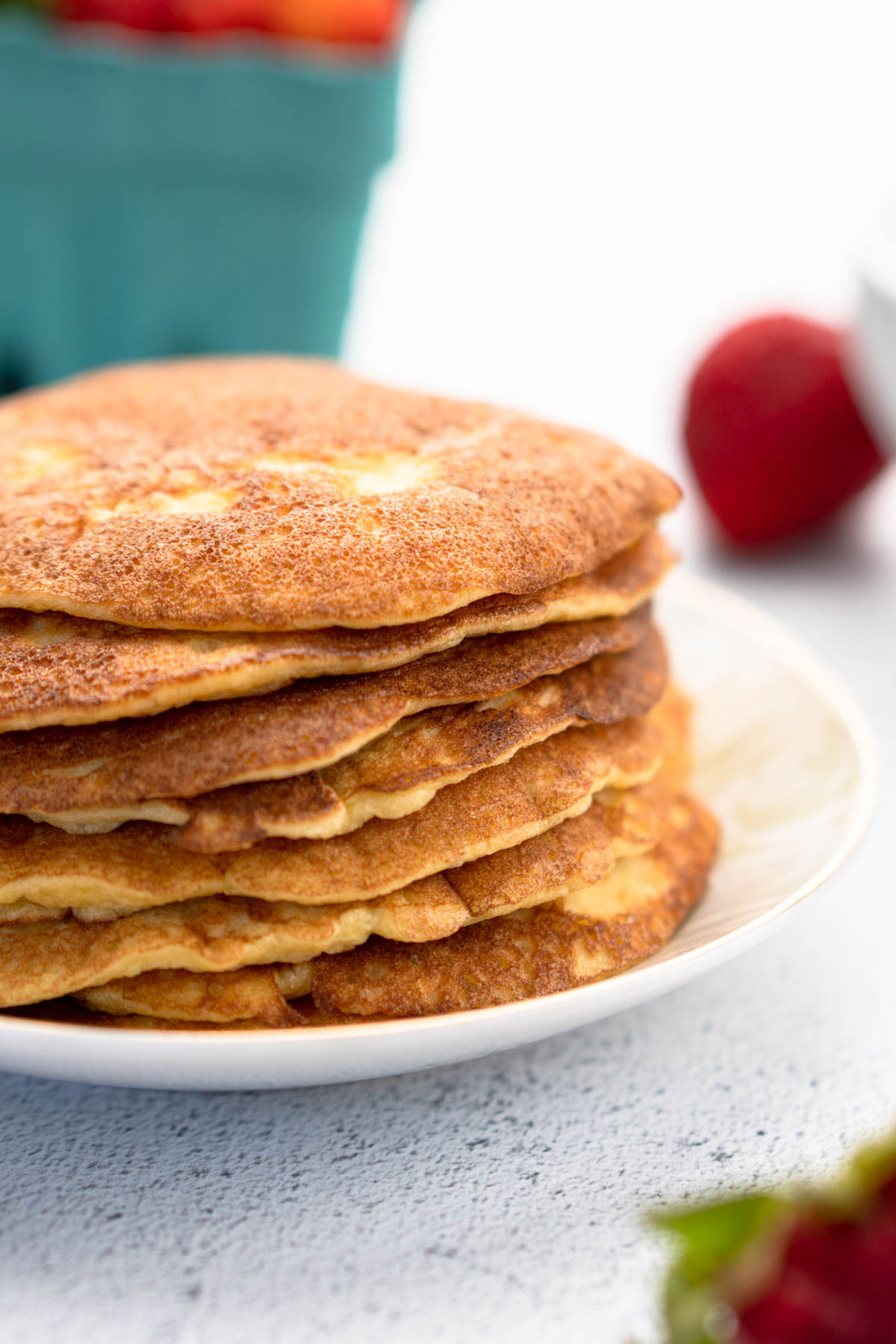 Pancakes stacked on a plate with fruit in the background.